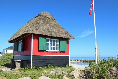 sky house building red flag roof water beach denmark marital